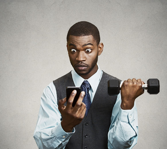 Closeup portrait shocked, surprised business man reading bad news on smart phone holding mobile, lifting weight, dumbbell isolated black background. Human face expression, emotion, corporate executive